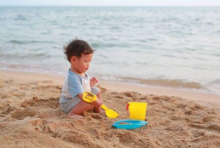 Little asian baby boy playing sand at beach alone. Фото со стока - 135458199