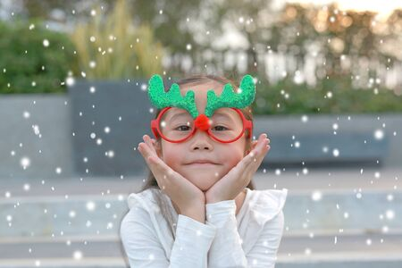 Close-up face of happy little girl reindeer with floating snow outdoor. Фото со стока - 135456278