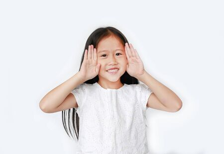 Portrait of happy little child girl gestures playing peekaboo over white background. Kid posture open hands from eyes with smile.