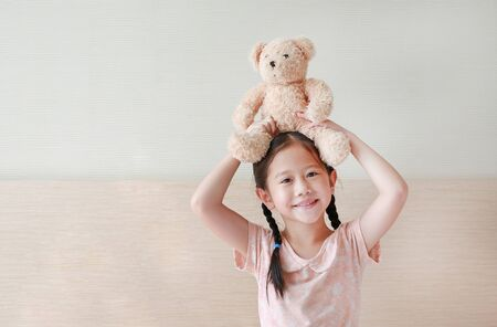 Happy Asian little girl showing teddy bears while sitting on the bed at home. Фото со стока - 135456310