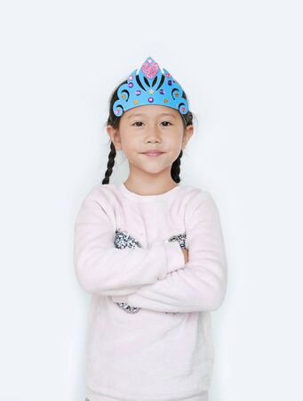Portrait of confident little Asian child girl with wearing a crown toys and cross one arm isolated over white background. Фото со стока - 135456209