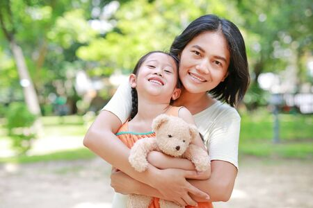 Portrait of happy Asian mother cuddle daughter and hugging teddy bear doll in the garden. Mom and child girl with love and relationship concept. Фото со стока - 135456255