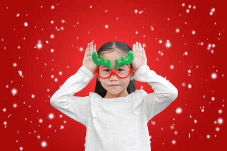 Cute little asian girl reindeer with floating snow on red christmas background. Фото со стока - 135456184