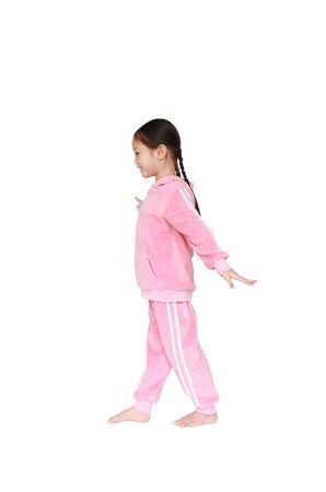 Portrait of smiling little Asian kid girl in pink tracksuit or sport cloth doing exercises isolated on white background. Фото со стока - 135456302