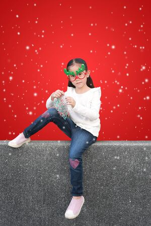 Portrait of little Asian girl sitting on pebble stone wall with holding multi-color paper spray against floating snow on red christmas background. A moment of celebration concept. Фото со стока - 135456323