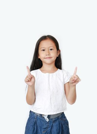Portrait of Asian little child girl raised two forefinger to cheer isolated on white background. Фото со стока - 135456289