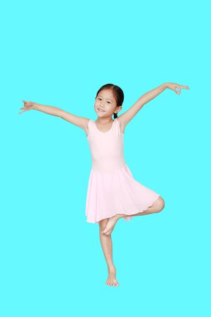 Beautiful little Asian child girl in pink tutu skirt isolated on cyan background. Children is studying ballet. Фото со стока - 135456291