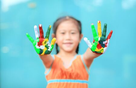Portrait of smiling little girl looking through her colorful hands. Focus at baby hands. Фото со стока - 135456149