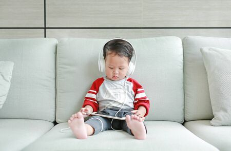 Adorable little Asian baby boy in headphones is using a smartphone lying on the sofa at home. Child listening to music on earphones. Stock Photo