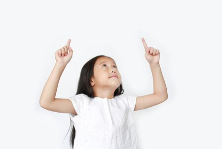Portrait of Asian little child girl pointing two forefinger up and looking above isolated over white background. Фото со стока - 135458337