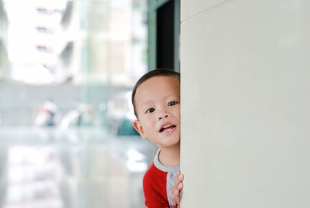 Cute little baby boy hide behind a corner room. Baby playing peekaboo game indoor. What a surprise.