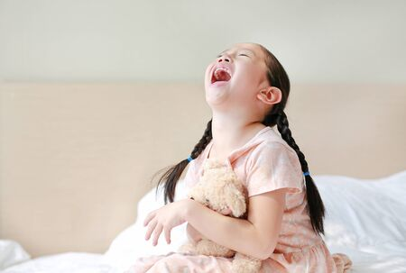 Funny of Asian little girl embracing teddy bear while sitting on the bed at home. Фото со стока - 135367763