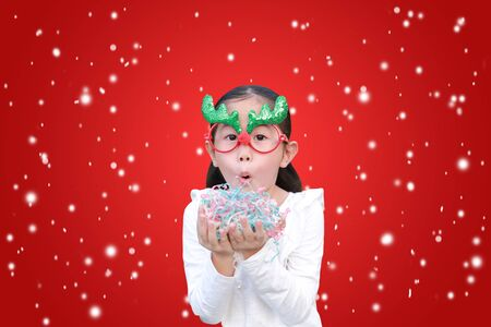 Funny little girl blowing a multi color paper spray in her hands against floating snow on red christmas background. A moment of celebration in winter season concept. Фото со стока - 135458312