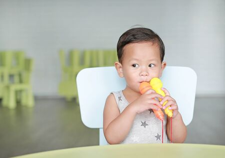 Smiling little Asian baby boy sing a song by plastic microphone at classroom.