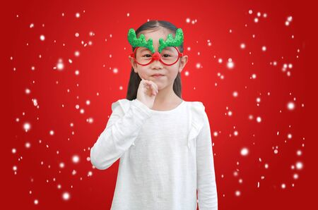 Happy little girl reindeer with floating snow on red christmas background. Фото со стока - 135456169