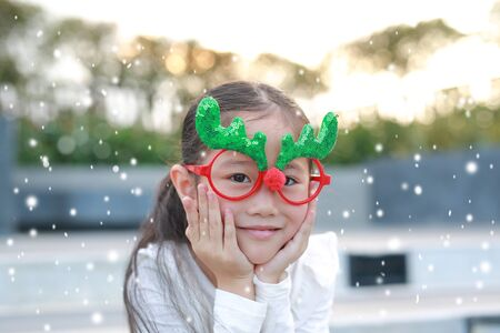 Close-up face of happy little girl reindeer with floating snow outdoor. Фото со стока - 135458368