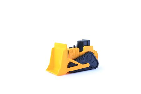 The yellow toy car Bulldozer isolated on white background. Children's tractor toy. Wheel loader construction car model. Фото со стока - 135367753