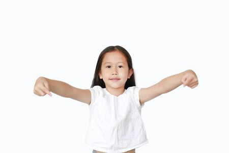 Portrait of little Asian child girl pointing down to present something isolated over white background. Asian schoolgirl in education concept. Фото со стока - 135458391