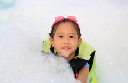 Portraits of happy little Asian child girl smiling having fun in Foam Party at the pool outdoor. Фото со стока - 135458331