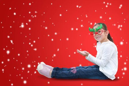 Happy little girl reindeer sitting and expression hands to get and support the snow on red christmas background with copy space. A moment of celebration in winter season concept.
