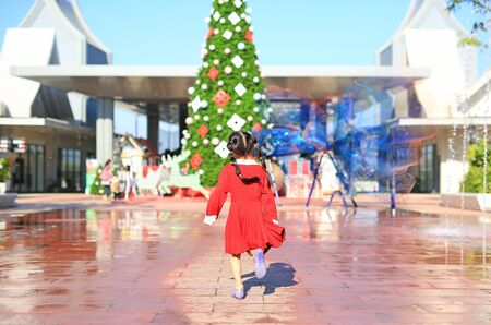Portrait of little girl in red dress running to the big christmas tree decorative for the happy new year and merry christmas festival. Rear view. Stok Fotoğraf
