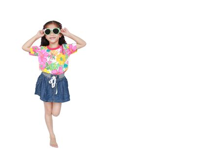 Smiling little Asian child girl wearing a floral pattern summer dress and sunglasses isolated on white background with copy space. Summer and fashion concept.