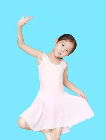 Beautiful little Asian child girl in pink tutu skirt isolated on cyan background. Children is studying ballet.