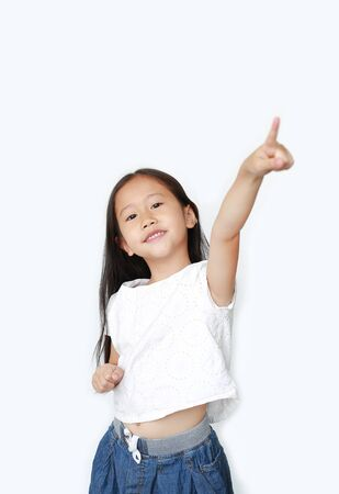 Portrait of happy little child girl poiting up and looking at camera isolated over white background.