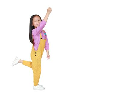 Happy little Asian child girl in pink-yellow dungarees freedom movement over white background with copy space. Kid activity concept. Фото со стока