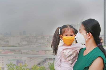 Mother carrying her daughter with wearing a protection mask against PM 2.5 air pollution in Bangkok city. Thailand.