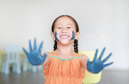 Happy little Asian girl with her blue hands and cheek painted in the children room.