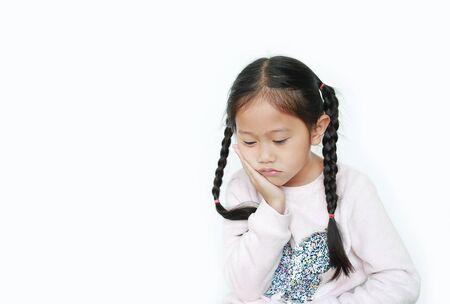 Ernstes und trauriges asiatisches kleines Kindermädchen mit Haltung ihre Hand auf Wange lokalisiert über weißem Hintergrund. Standard-Bild