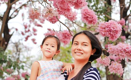 Portrait little girl and her mom with Beautiful Tabebuia rosea blooming in spring season at garden outdoor.