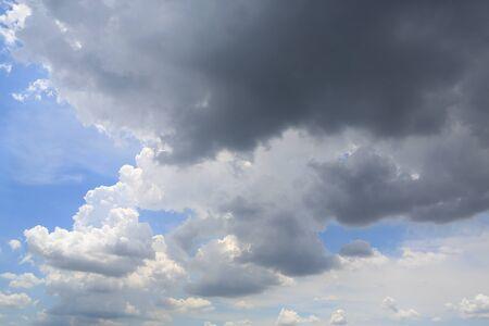 Dark clouds before rain on blue sky background.
