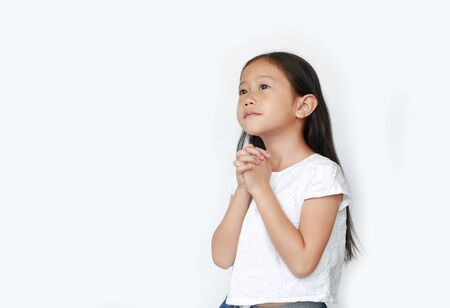 Beautiful little asian child girl praying isolated over white background with looking up. Spirituality and religion concept.