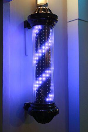 Barber pole turning swirl LED light sign in dark background Фото со стока