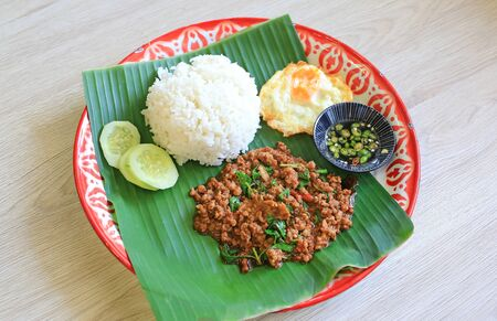 Stir-fried minced pork with basil leaves served with rice and fried egg on banana leaf on zinc tray over wooden table background.