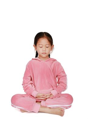 Cute little asian child girl in pink tracksuit with eyes closed practicing mindfulness meditation sitting on white background. Peaceful concept. Standard-Bild