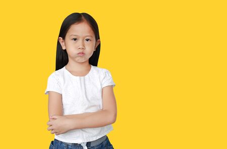Cute little hispanic Asian child girl with arms crossed and angry about something on yellow background with copy space. Person with Negative emotion concept.