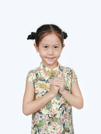 Beautiful Asian little girl wearing cheongsam with smiling and welcome gesture celebrating for happy Chinese New Year isolated on white background.