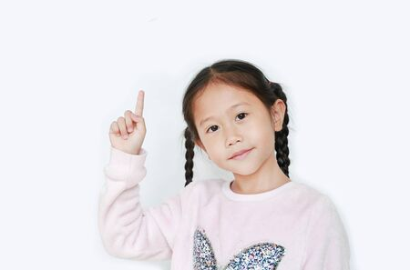 Cute little child girl point forefinger up present something isolated over white background. Asian schoolgirl in education concept.