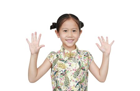 Portrait of Asian little girl wearing cheongsam with smiling and shows two palms, give five isolated over white background. Фото со стока
