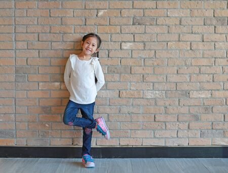 Attractive Asian little girl with pigtail hair in jeans and a white shirt standing at brick wall background with copy space.