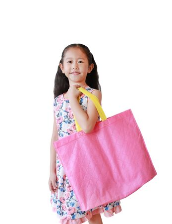 Beautiful Asian little girl carrying a pink recycle bag isolated over white background. Eco friendly bag for reduce or zero waste concept. Фото со стока