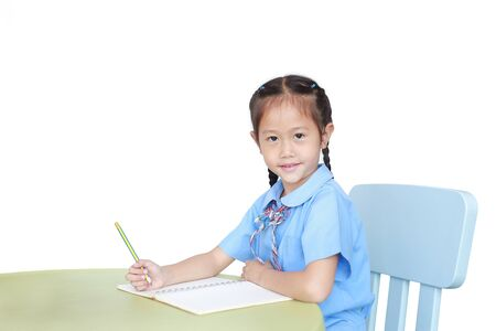 Smiling Asian little girl in school uniform writing on notebook at desk isolated on white background. Schoolgirl and Education concept.