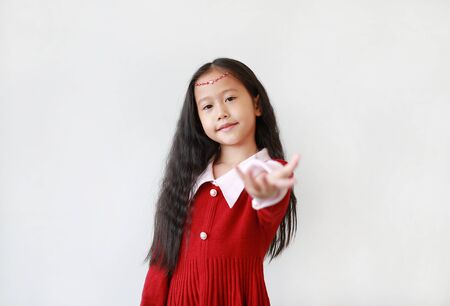 Portrait of pretty little girl in princess dress with smiling and expression open hand greeting and welcome you over white background.