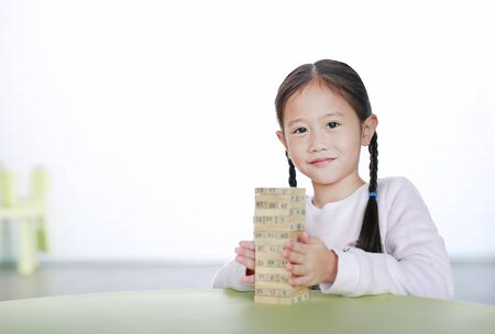 Portrait of little child girl playing wood blocks tower game for Brain and Physical development skill in a classroom. Focus at children face. Kid learning and mental skills concept. Фото со стока