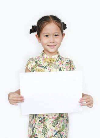 Portrait of Asian little girl wearing cheongsam with smiling and holding blank white paper isolated on white background.