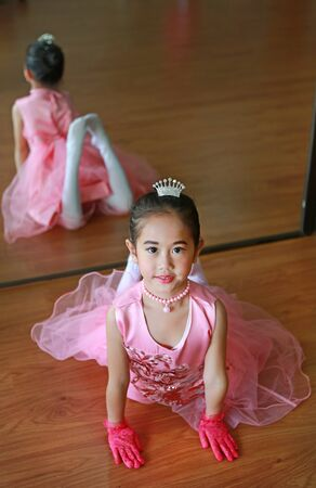 Adorable little ballerina girl in a pink tutu lying on the floor with looking at camera.