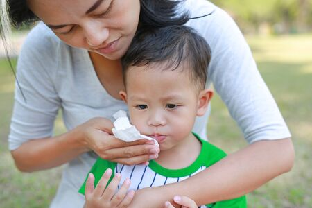 Close-up Asian mother wipe baby mouth by tissue in the garden outdoor.